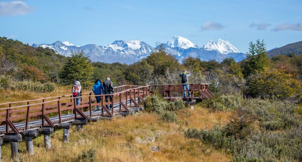 Tourists walk along an elevated walkway through a nature preserve at Bahia Lapataia in the Tierra del Fuego National Park.